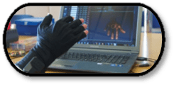 Hand wearing sensory glove in front of a laptop screen